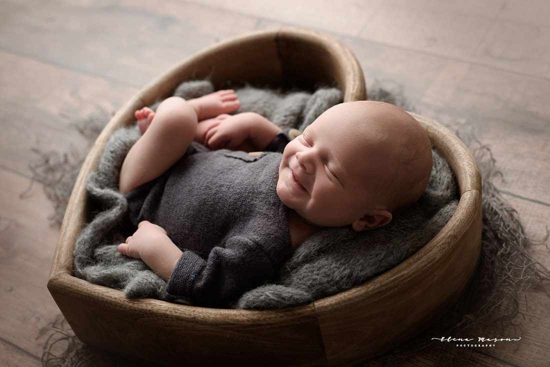 sleeping baby in heart bowl on grey, smiling baby, newborn photo session, newborn photography Belfast
