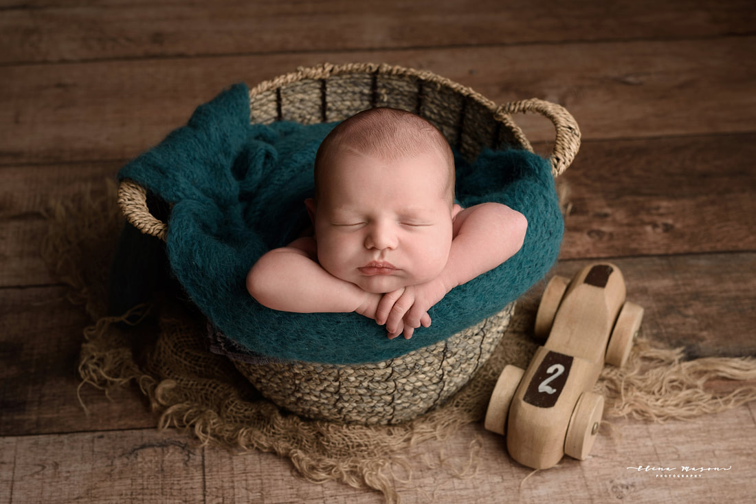newborn baby in blue in bucket, newborn photo session Belfast